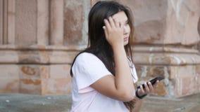 video 4k di bella ragazza con lo smartphone che si siede sulla vecchia scala di pietra video d archivio