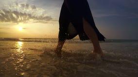 video 4K: Piedi del ` s della donna mentre lei ` s che cammina lungo il litorale archivi video