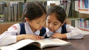 video 4K: Små asiatiska studenter som bär likformig och läseboken i arkiv lager videofilmer