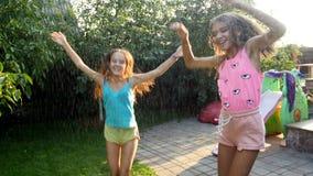 Video 4k von zwei glücklichen lachenden Jugendlichen, die unter das Wasser sprüht vom Gartenwasserschlauch tanzen stock video