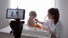 Video lesson, blogger mother medic examining son using stethoscope and leads live learning broadcast on smartphone for stock footage