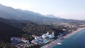 video Luchtmening van Hotel op overzeese die kust en bergen met groen bos, bomen met blauwe hemel bij zonsopgang worden behandeld stock footage
