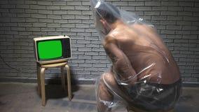 Video of man in package watching retro tv. Video of man watching retro tv on wall background stock video