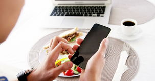 Video of man using smartphone with lunch stock footage