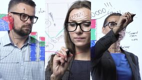 3 in 1 video. Man and woman draws various growth charts, calculating prospects for success in a modern glass office. 3 in 1 video. Businessman and businesswoman stock footage