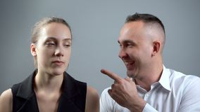 Video of mocking woman on grey background. Video of man and woman sitting near on grey background stock video footage