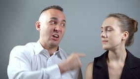Video of screaming man at woman on grey background. Video of man and woman sitting near on grey background stock footage