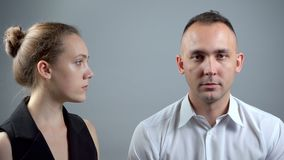 Video of angry wife and husband on grey background. Video of man and woman sitting near on grey background stock video footage