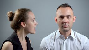 Video of screaming woman at man on grey background. Video of man and woman sitting near on grey background stock footage