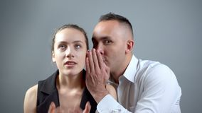Video of two gossipers on grey background. Video of man and woman sitting near on grey background stock video