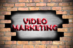 Video marketing in the hole of brick wall Stock Image