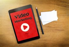 Video Marketing on mobile device screen with pen and business ca. Rd on wood table,Digital marketing concept Stock Photo