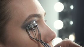 Video of master using eyelash curler. Video of visagist using eyelash curler in beauty studio stock footage