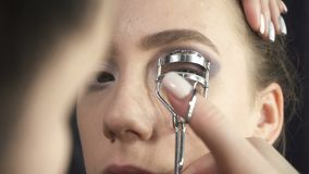 Video of master using eyelash tongs. Video of visagist using eyelash curler in beauty studio stock video footage