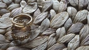 Video movie Wedding rings accessory lying on straw table. Close up. top view.  stock video