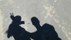 Video ombre divertenti Due persone ondeggiano le loro mani, costruiscono i corni sulle loro teste ed esaminare le loro ombre Camm video d archivio