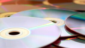 Panning shot of a pile of DVDs on a table. Video of panning shot of a pile of DVDs on a table stock video