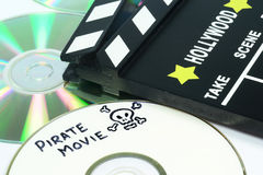 Video piracy. Pirate Movie written on a dvd next to a clapper board Royalty Free Stock Image