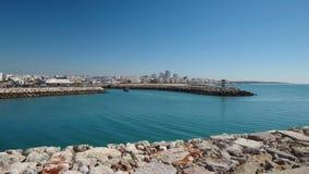 _ Video pirfiskeport, skepp seglar in i fjärden, staden Quarteira arkivfilmer