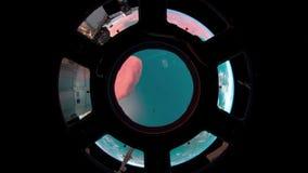 2 video in1 Planetjord som ses från ISSEN Jord till och med hyttventilen av ISSEN Beståndsdelar av denna video som förbi möbleras arkivfilmer