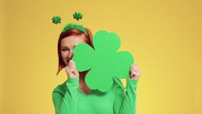Playful woman holding clover shaped banner with copy space