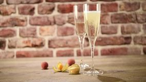 Video of poring champagne into two flutes  on the wooden table with the brick background, selective focus stock video footage