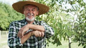 Handheld video portrait of happy farmer in a straw hat.