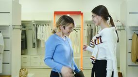 Video portrait of Pretty Stylish and fashionable female friends showing to camera silver sale tone in fashion boutique
