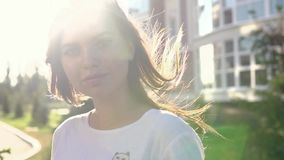 Video portrait young beautiful teenage girl smiling walking on the city street. HD stock video