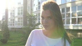 Video portrait young beautiful teenage girl smiling walking on the city street. HD stock footage