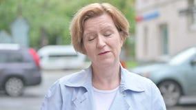 Video pratstund av den gamla kvinnan som står utomhus- lager videofilmer