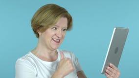 Video pratstund av den gamla kvinnan via minnestavlan som isoleras på blå bakgrund arkivfilmer