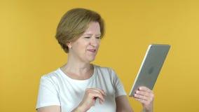 Video pratstund av den gamla kvinnan via minnestavlan som isoleras på gul bakgrund lager videofilmer