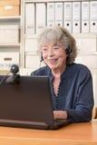 Video pratstund för grå haired kvinna Arkivfoton