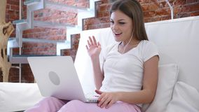 Video pratstund för rengöringsduk på bärbara datorn av den unga kvinnan som sitter på trappa Arkivfoto