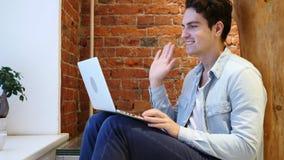 Video pratstund för rengöringsduk på bärbara datorn av den unga mannen som sitter på trappa Royaltyfria Bilder