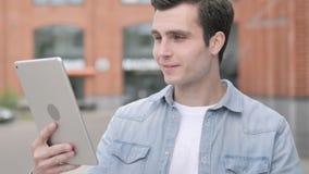 Video pratstund på minnestavlan vid det utomhus- anseendet för ung man lager videofilmer