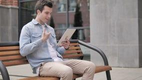 Video pratstund på minnestavlan vid tillfälligt sitta för ung man som är utomhus- stock video