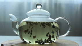 Video of Process of brewing green Chinese tea in a glass teapot. On wooden background