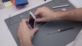 Video processo di mostra del primo piano della riparazione del telefono cellulare video d archivio