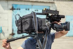 Video production, cameraman or operator with professional movie camera equipment at work outdoors, television broadcast. And cinematography concept royalty free stock photography