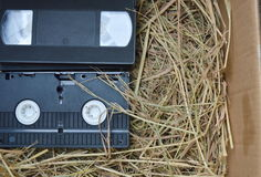 Video recorder cassette on straw in the box Royalty Free Stock Photo