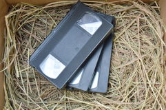 Video recorder cassette on straw in the box Stock Photos