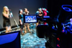 Video recording of the concert. Girls sing in microphones. Camcorder with LCD display. Shooting in the interior. Studio or on stage stock image