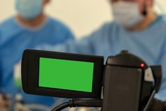 Video recording and live broadcast of the work of two surgeons. Operating room surgical hospital. Green screen camcorder. Copy stock images