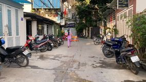 Video recording during motorbike ride on street of Nha Trang. Nha Trang, Vietnam - 18 February 2019: sunny narrow city street with many parked multicolored stock footage