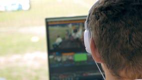 Video redattore di radiodiffusione con le cuffie contro lo schermo archivi video