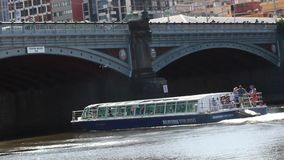A river boat going under a bridge in central. Video of A river boat going under a bridge in central stock footage