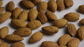 Rotating shot of almonds on a white surface. Video of rotating shot of almonds on a white surface stock footage
