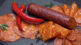 Salami and chorizo sausage close up on dark concrete background. Video of salami and chorizo sausage close up on dark concrete background stock video